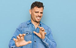 Young hispanic man wearing casual denim jacket disgusted expression, displeased and fearful doing disgust face because aversion reaction. with hands raised