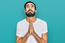 Young hispanic man wearing casual white t shirt begging and praying with hands together with hope expression on face very emotional and worried. begging.