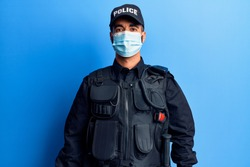 Young hispanic man wearing police uniform and medical mask with a happy and cool smile on face. lucky person.