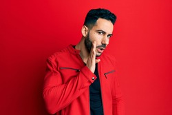 Young hispanic man wearing red leather jacket hand on mouth telling secret rumor, whispering malicious talk conversation