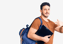 Young hispanic man wearing student backpack holding binder pointing finger to one self smiling happy and proud