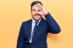 Young hispanic man wearing suit doing ok gesture with hand smiling, eye looking through fingers with happy face.