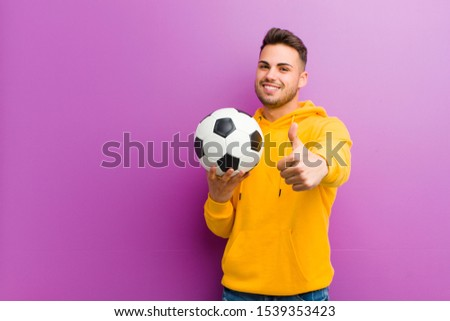 young hispanic man with a soccer ball against purple background