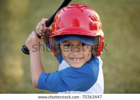 Young hispanic or latino boy with red baseball helmet over a blue hat and blue tee shirt. - stock photo