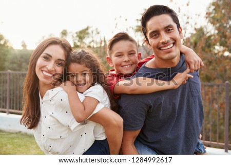 Young Hispanic parents piggyback their children in the park, smiling to camera, focus on foreground #1284992617