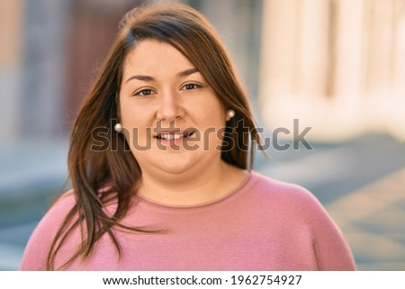 Young hispanic plus size woman smiling happy standing at the city. Foto stock ©
