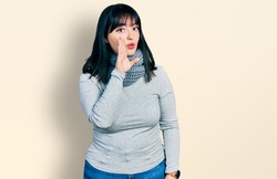 Young hispanic plus size woman wearing winter scarf hand on mouth telling secret rumor, whispering malicious talk conversation