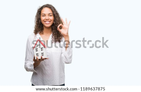 Young hispanic real state agent woman holding small house doing ok sign with fingers, excellent symbol #1189637875