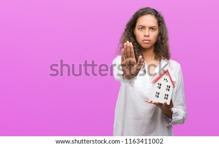 Young hispanic real state agent woman holding small house with open hand doing stop sign with serious and confident expression, defense gesture #1163411002
