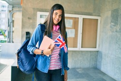 Young hispanic student girl smiling happy holding book and uk flag at the university.