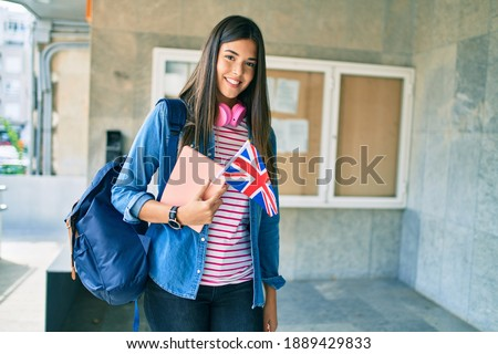 Young hispanic student girl smiling happy holding book and uk flag at the university. Foto stock ©