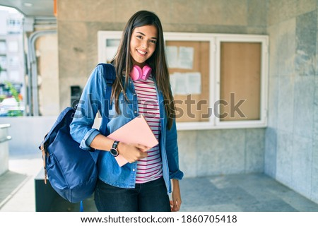 Young hispanic student girl smiling happy using headphones at the university.