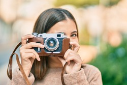 Young hispanic tourist woman smiling happy using vintage camera at the city.