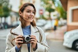 Young hispanic tourist woman smiling happy using vintage camera at the city