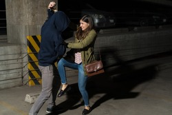 Young Hispanic woman defending herself from attacking thief in alley
