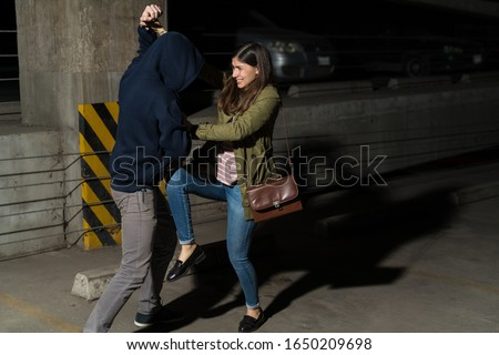 Young Hispanic woman defending herself from attacking thief in alley Stock photo ©