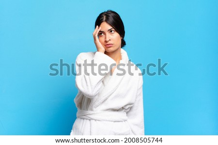 young hispanic woman feeling bored, frustrated and sleepy after a tiresome, dull and tedious task, holding face with hand. bathrobe concept Сток-фото ©