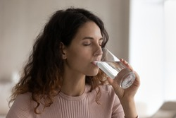 Young Hispanic woman hold glass drink pure mineral clean water recommend healthy lifestyle. Millennial Latino female enjoy clear aqua feel dehydrated thirsty. Hydration, healthy lifestyle concept.