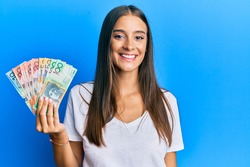 Young hispanic woman holding australian dollars looking positive and happy standing and smiling with a confident smile showing teeth