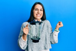 Young hispanic woman holding food processor mixer machine screaming proud, celebrating victory and success very excited with raised arm