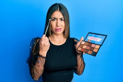Young hispanic woman holding makeup brush and blush skeptic and nervous, frowning upset because of problem. negative person.