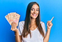 Young hispanic woman holding mexican pesos smiling happy pointing with hand and finger to the side