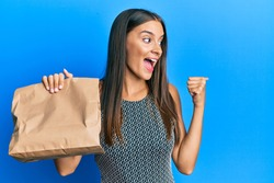Young hispanic woman holding take away paper bag pointing thumb up to the side smiling happy with open mouth