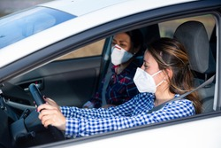 Young Hispanic woman in medical face mask driving car with female friend in front passenger seat. Concept of new life reality and health protection in coronavirus pandemic