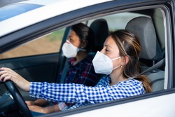Young Hispanic woman in medical face mask driving car with female friend in front passenger seat. Concept of new life reality and health protection in coronavirus pandemic..