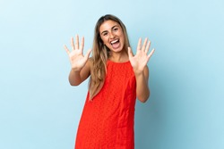Young hispanic woman over isolated blue background counting ten with fingers