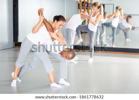 Young hispanic woman practicing basic protection skills with man during self defense course in gym Stock photo ©