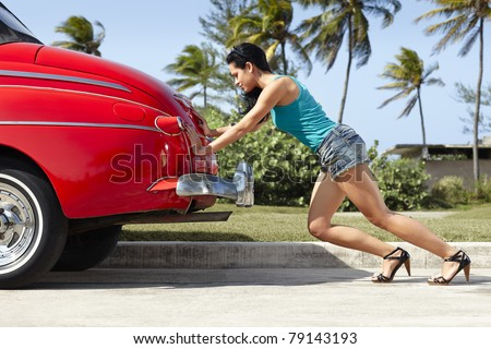young hispanic woman pushing broken down red convertible vintage car. Horizontal shape, full length, side view