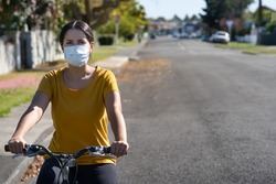 Young hispanic woman riding her bicycle and wearing a face mask against covid-19