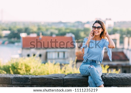 Young hispanic woman sitting on the wall and talking on mobile phone