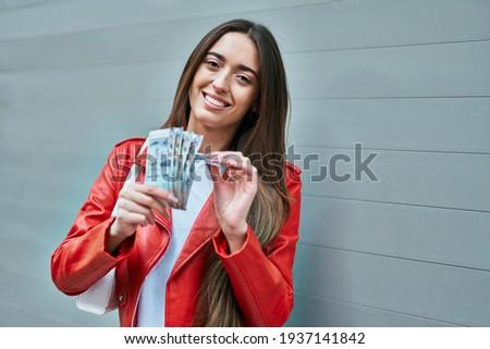Young hispanic woman smiling happy counting peruvian sol banknotes at the city. Foto stock ©