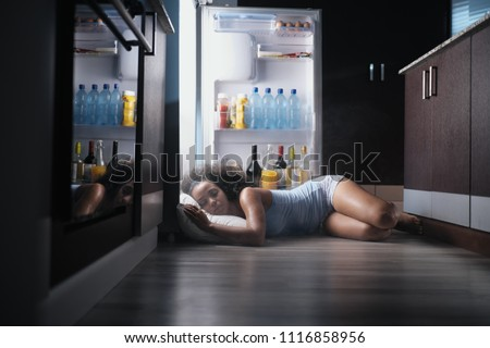 Young hispanic woman suffering for summer heat and lack of air conditioning at home. Black girl covered with sweat sleeping on floor with head inside fridge.