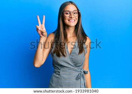 Young hispanic woman wearing business dress and glasses smiling with happy face winking at the camera doing victory sign. number two.  Photo stock ©