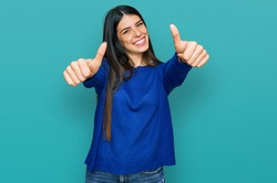 Young hispanic woman wearing casual clothes approving doing positive gesture with hand, thumbs up smiling and happy for success. winner gesture.