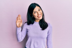 Young hispanic woman wearing casual clothes waiving saying hello happy and smiling, friendly welcome gesture