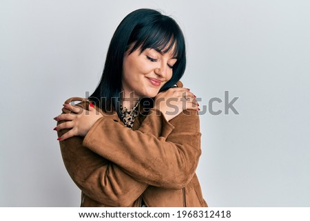 Young hispanic woman wearing casual leather jacket hugging oneself happy and positive, smiling confident. self love and self care  Foto stock ©