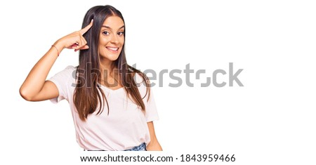 Young hispanic woman wearing casual white tshirt smiling pointing to head with one finger, great idea or thought, good memory  Foto stock ©