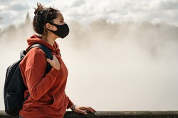 Young hispanic woman wearing face mask and touring on city with thermal activity. New Tourism and Coronavirus concept.