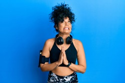 Young hispanic woman wearing gym clothes and using headphones begging and praying with hands together with hope expression on face very emotional and worried. begging.