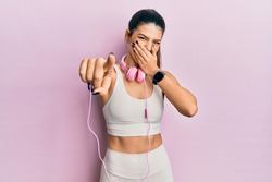 Young hispanic woman wearing gym clothes and using headphones laughing at you, pointing finger to the camera with hand over mouth, shame expression