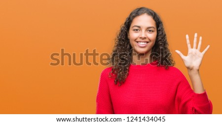 Young hispanic woman wearing red sweater showing and pointing up with fingers number five while smiling confident and happy. #1241434045