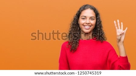 Young hispanic woman wearing red sweater showing and pointing up with fingers number four while smiling confident and happy. #1250745319
