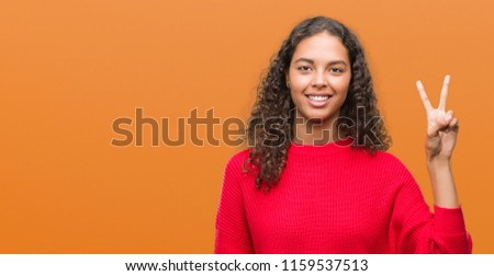 Young hispanic woman wearing red sweater showing and pointing up with fingers number two while smiling confident and happy. #1159537513