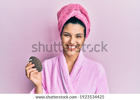 Young hispanic woman wearing shower bathrobe holding pumice stone looking positive and happy standing and smiling with a confident smile showing teeth  Stockfoto ©