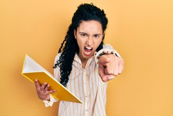 Young hispanic woman with curly hair holding book pointing displeased and frustrated to the camera, angry and furious with you