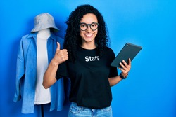 Young hispanic woman with curly hair wearing staff t shirt holding touchpad device smiling happy and positive, thumb up doing excellent and approval sign